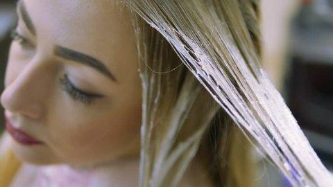 Stylist Studio beauty cause hair dye on blond strands. Closeup