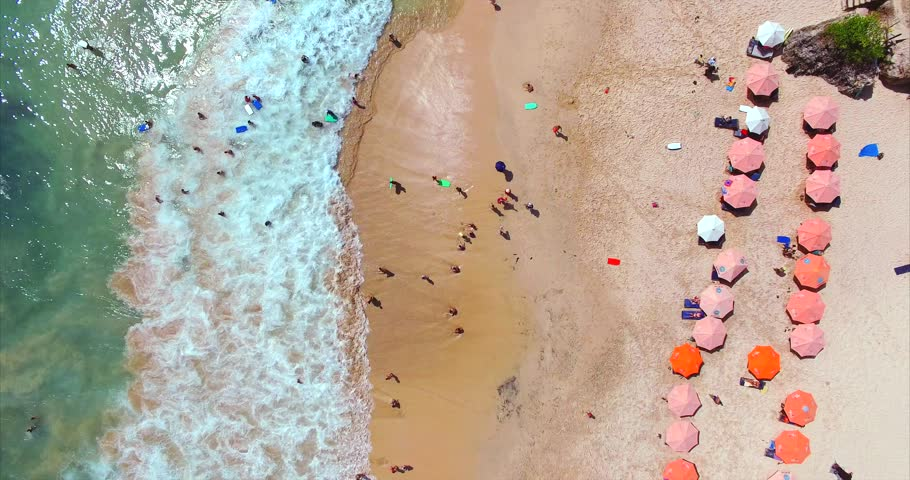 Umbrellas, deck chairs and tourists relaxing on the beach. Dreamland famous balinese beach. Aerial top view. Bali, Indonesia