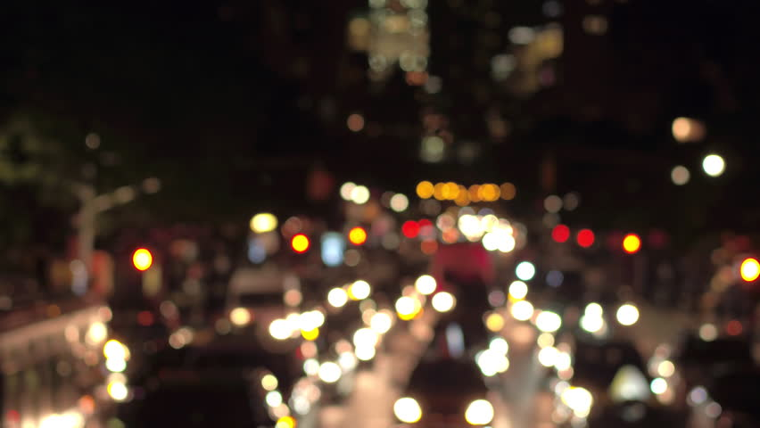 DEFOCUSED BOKEH: Traffic jam on busy road in crowded New York City street during the night. Colorful blurred car headlights and flashing traffic lights glowing in the dark creating magical atmosphere