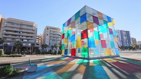Malaga, Spain - December 15 2016: Colorful glass cube wich is entrance to Centre Pompidou, located in renovated port area of Malaga