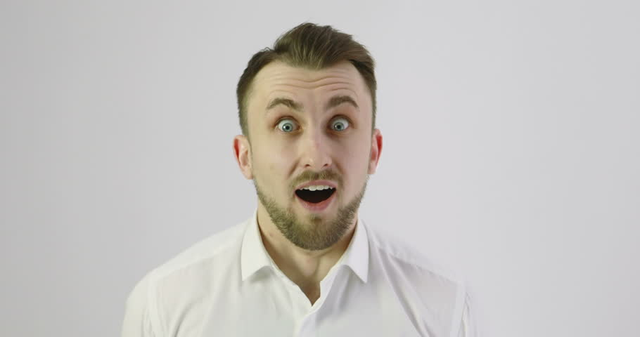 4K Close up of a surprised emotional man looking into the camera. Portrait of a handsome young guy in a white shirt.