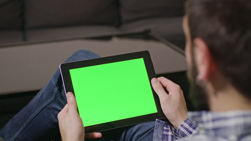 Young man using digital tablet pc with blue screen sitting at home. sliding | Shutterstock HD Video #23961382