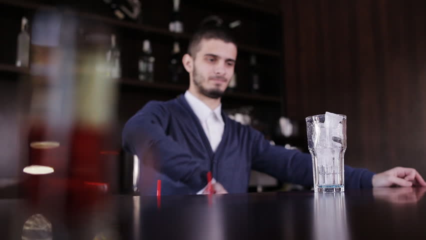 Bartender with shaker making cocktail in modern bar. Handsome barman shake drink.. Handsome barman professional at posh bar making cocktail drinks.