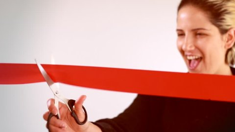 Smiling woman cutting red ribbon