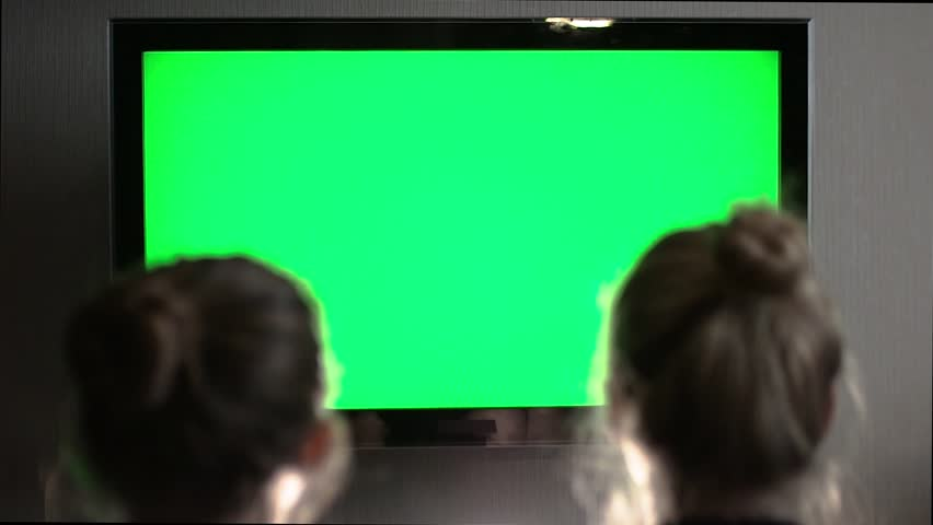 Two young long-haired blond looking at green screen TV in evening home interior.