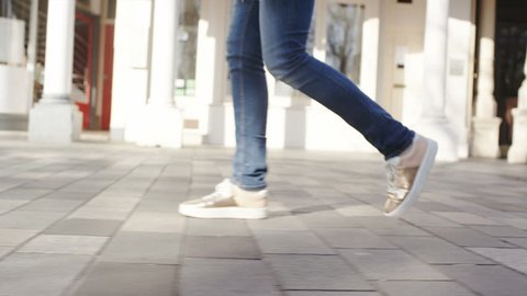 4K Camera follows the feet of a female walking through town, in slow motion