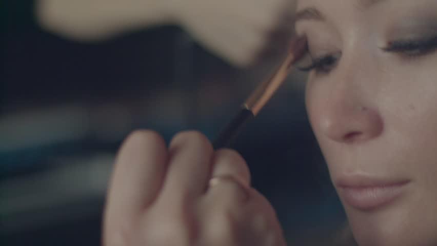 Using makeup brush to apply eye shadows handheld close up 4k slow motion. Professional make-up artist visagiste puts light brown shadows on eyelid finish makeup. False eyelashes blue eyes look macro