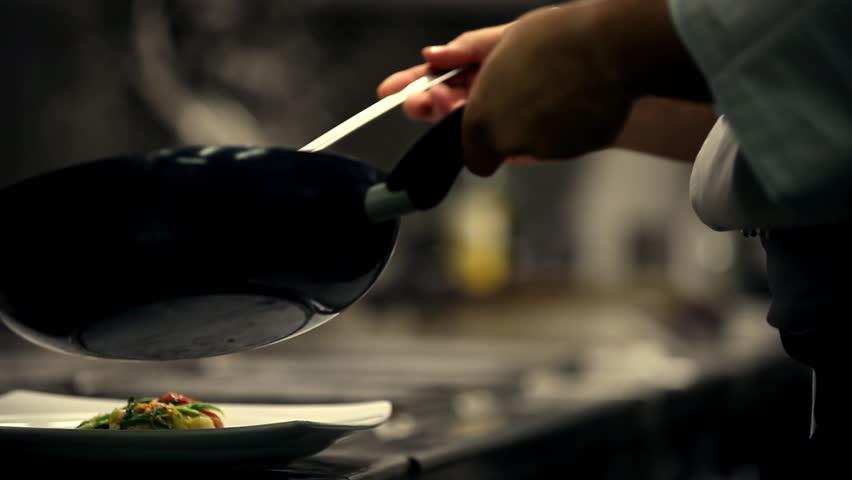Chef prepares a dish in a restaurant kitchen