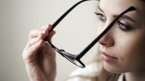 Beautiful woman puts on stylish glasses. Girl wears eyeglasses. Beautiful young woman wearing black glasses. Glasses closeup. Beautiful girl in glasses
