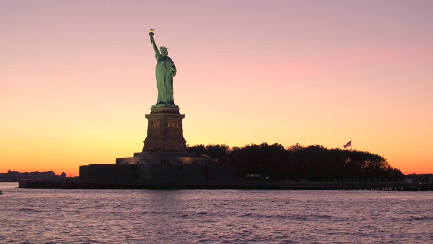 CLOSE UP LOW ANGLE VIEW Iconic Lady Liberty - the Statue of Liberty National Monument in New York Harbor against breathtaking golden sky at twilight. Famous copper sculpture resplendent in golden hues | Shutterstock HD Video #24065272