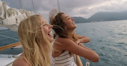 Beautiful girl friends laughing funny on sailboat in ocean on luxury lifestyle happy adventure travel vacation