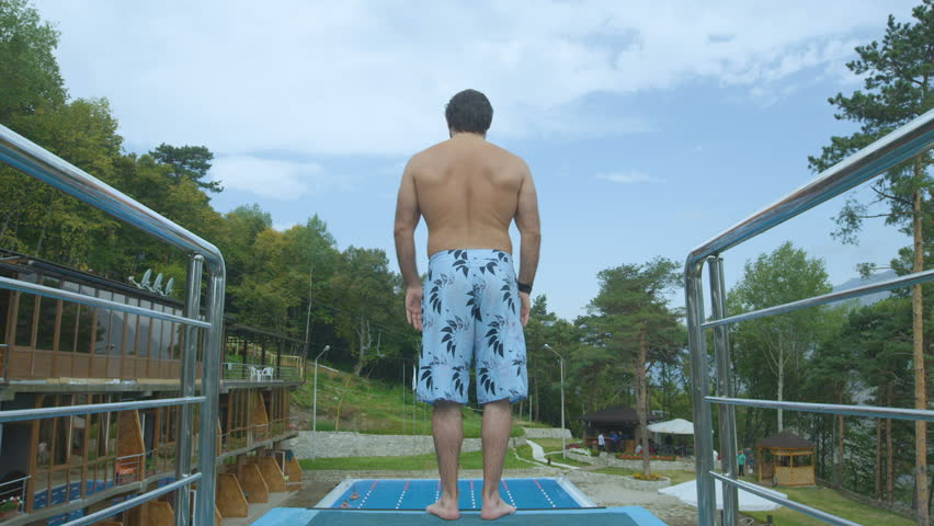 backside slow motion young man stands on swimming pool tower edge ready to jump and camera follows jumping #24085537