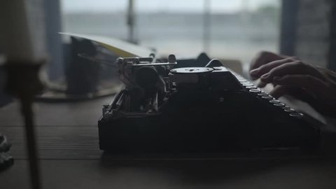 Man typing text on old typewriter.