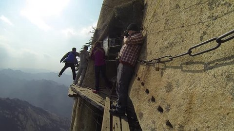 Walking the deadly Mount Huashan plank walk in the sky, clinging to the cliff side whilst walking along a path 2000ft in the air in China`s Mt Huashan`s highest peaks, Shanxi province, central China