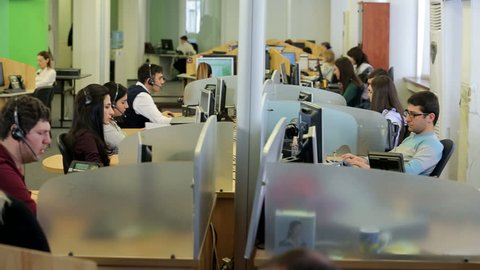 Row of call center operators at work. Customer services call centre team on telephones and computers .  High quality HD video footage
