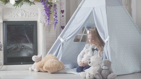 Little cute girl with blond hair sitting in a toy house surrounded by soft toys. Girl playing with a toy hare and a soft teddy bear. Little girl in teepee tent hug her teddy bear