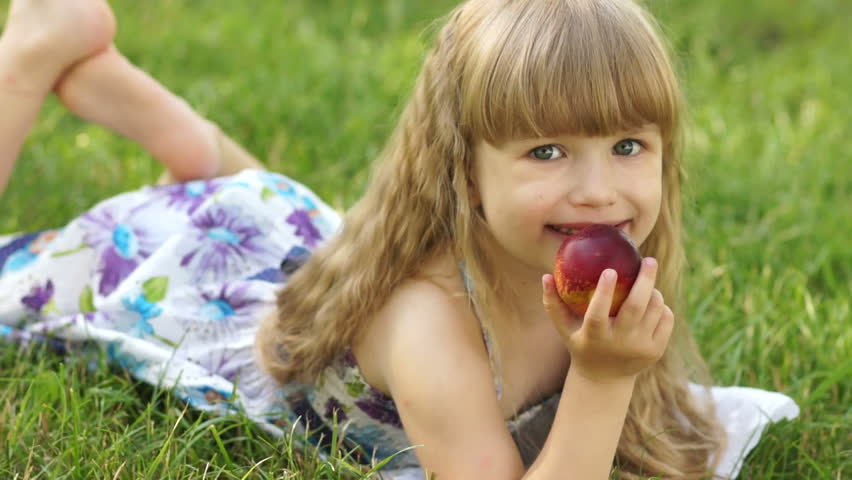 Girl lying on the grass and eating a peach