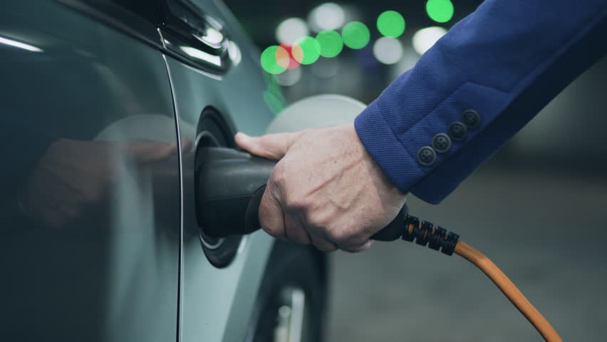 Senior is plugging power cord to an electric car. Close up. 4K | Shutterstock HD Video #24136654