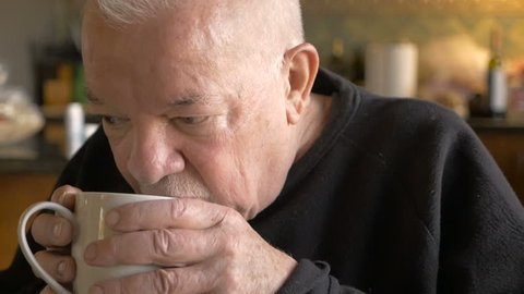 An attractive aging senior man drinking a cup of hot coffee or tea in slow motion
