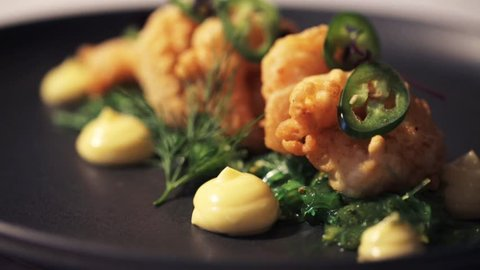 close up of king prawns with jalapeno, wasabi mayonnaise and wakame salad on plate