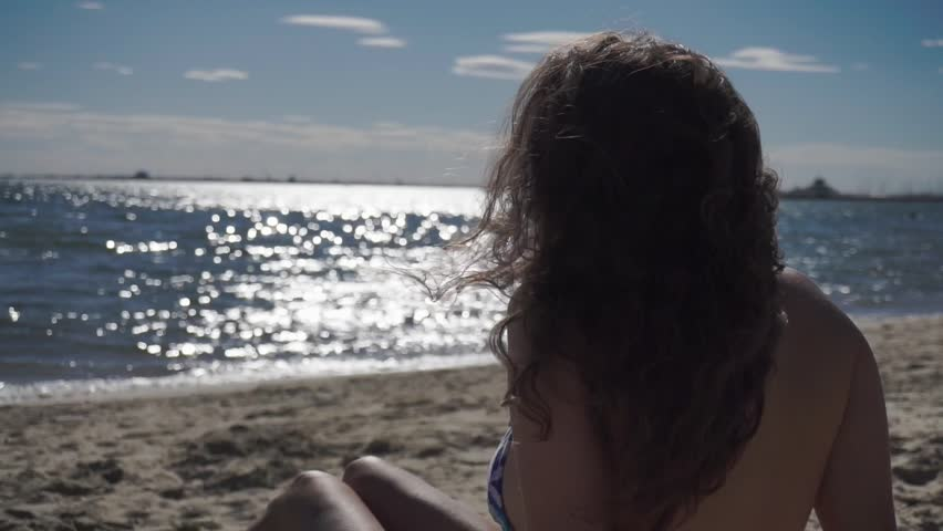 Latin girl sunbathing on the beach and watching the sea in Melbourne | Shutterstock HD Video #24182722