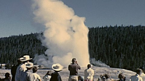YELLOWSTONE NATIONAL PARK - 1965: people watch a geyser in 1965 Yellowstone National Park