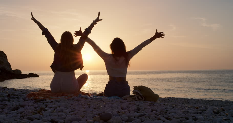Two young woman arms raised discovering beautiful tropical beach teenager girls enjoying nature together as best friends celebrating summer vacation