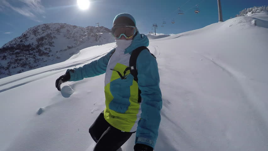 SELFIE CLOSE UP: Snowboarder riding powder snow off piste in sunny ski resort #24202612