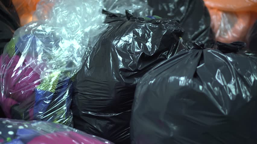 A pan of garbage bags, holding donated clothing.