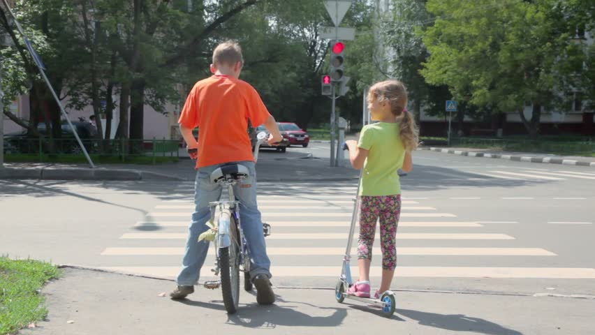 Boy sits on bicycle and his sister stands with scooter at pedestrian crossing