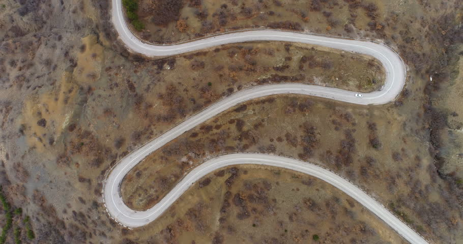 White car goes on serpentine road. Green hills. Aerial view. Flying upward. | Shutterstock HD Video #24218032