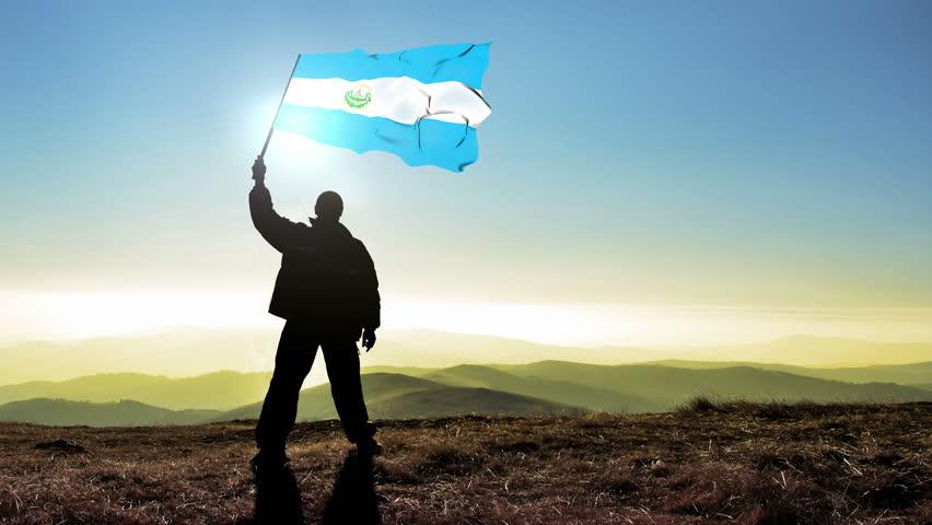 Successful silhouette man winner waving El Salvadorian flag on top of the mountain peak. Cinemagraph LOOP background