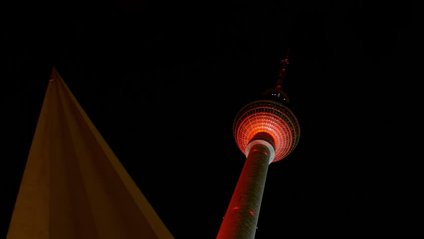 Berlin TV Tower and Triangular Roof element with Lightshow at Night Berlin TV Tower Fernsehturm at Night, Tower with colorful, red, pink and blue light projection that moves rhythmically.
