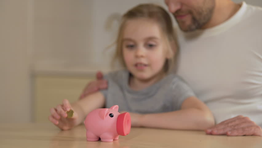 Father teaching little daughter to save money in piggy bank, giving high five