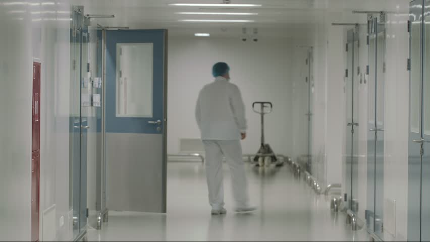 One scientist or doctor walking down the hall at modern pharmaceutical factory. Rear view. | Shutterstock HD Video #24237302