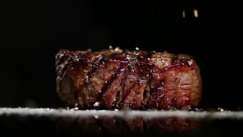 SLOW MOTION FOOD: large grains of pepper fall on juicy grilled filet mignon close up | Shutterstock Video #24250295