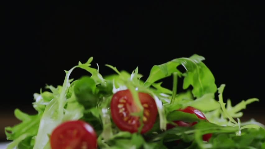 SLOW MOTION FOOD: red juicy tomatoes falling on green lettuce leaves on a black background