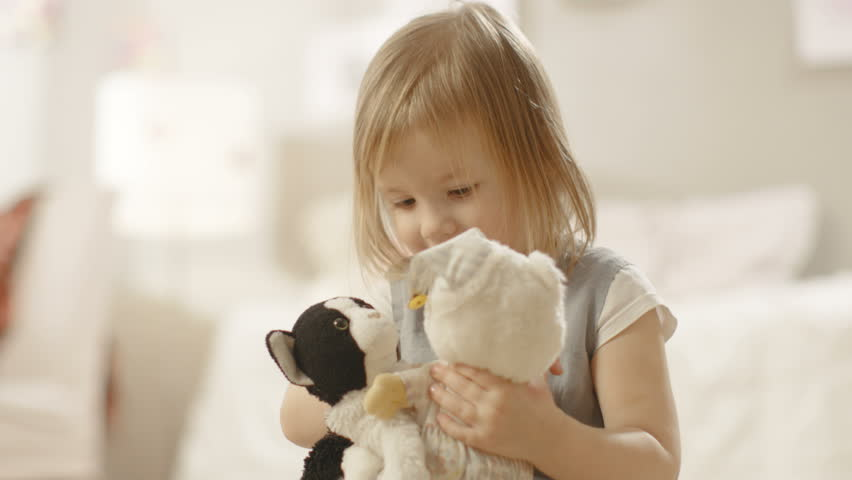 Happy Little Girl Plays with Plush Toys in Her Room. Shot on RED EPIC-W 8K Helium Cinema Camera.