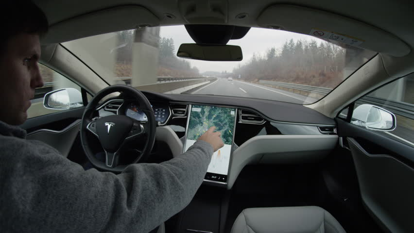 LJUBLJANA, SLOVENIA - FEBRUARY 4, 2017: Autonomous robotic car self-driving on highway. Driver routing, planning, selecting the path on navigation touchscreen in luxury Tesla Model S electric vehicle