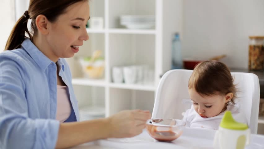 family, food, child, eating and parenthood concept - mother with puree and spoon feeding little baby sitting in highchair at home kitchen