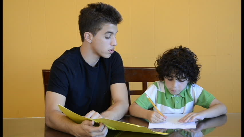 Latin boys studying together at home. Eldest son helps his brother with homework