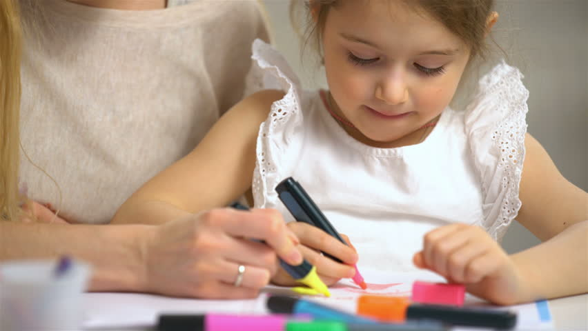 Little girl draws in the nursery. Mother looking how her child daughter drawing a picture   Shutterstock HD Video #24299795