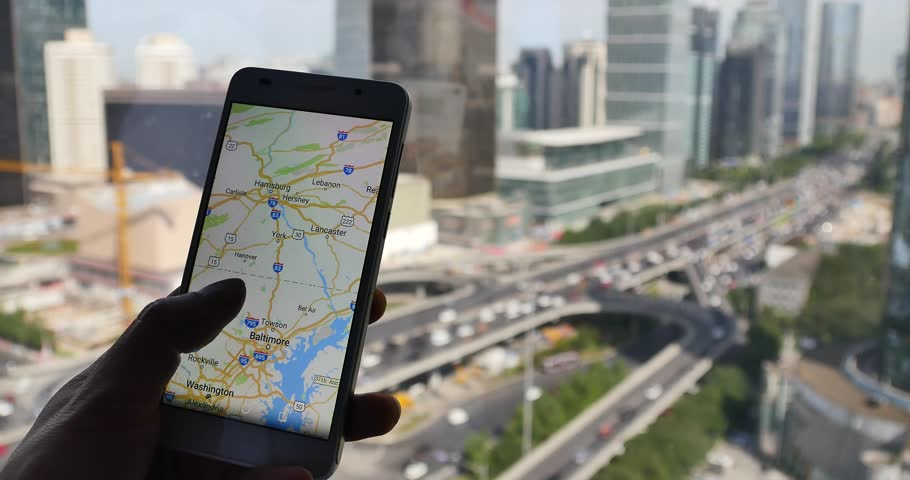 BeiJing,China - Oct 2016:4k,human browse map on smartphone with business building & urban traffic background. gh2_11600_4k