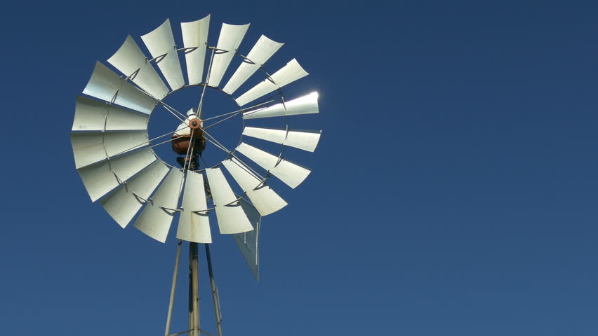 A spinning windmill against blue skies