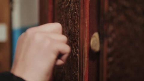 Close-up of hand knocking on door