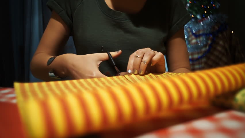 Female cutting yellow with orange stripes wrapping paper for packing presents.