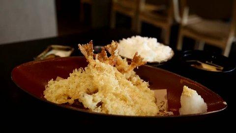 woman's hand using chopstick to eat deep fried prawn shrimp, tempura Japanese food, in restaurant.