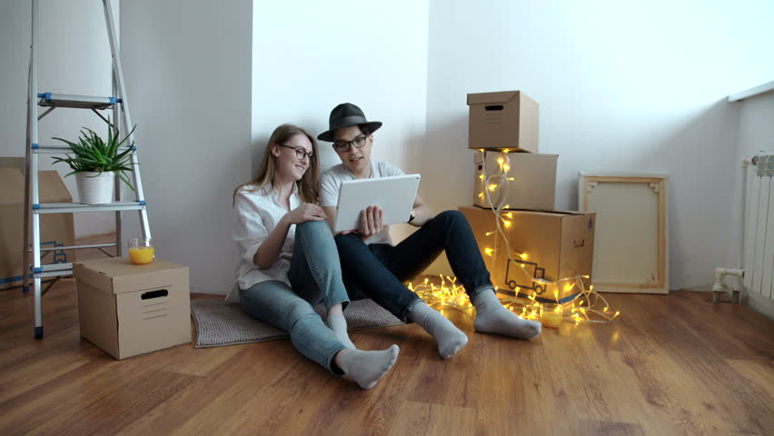 Young couple moving in new home.Sitting on floor and relaxing after cleaning and unpacking.Using tablet. | Shutterstock HD Video #24327872