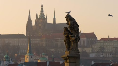 PRAGUE - FEB 10, 2017: Prague castle and a statue on the bridge at sunset in winter