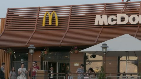 MINSK, BELARUS - JUL 27, 2016: Ungraded: People come and go in the door of the restaurant McDonald's summer day. Source: Lumix DMC, ungraded H.264 from camera without re-encoding. (av35493u)
